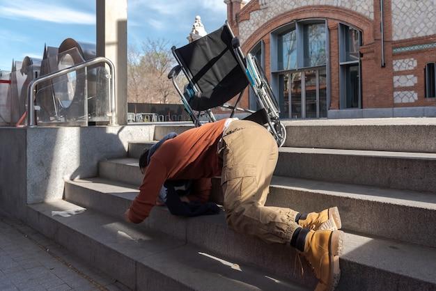 Niepełnosprawny młody człowiek na wózku inwalidzkim spada po schodach
