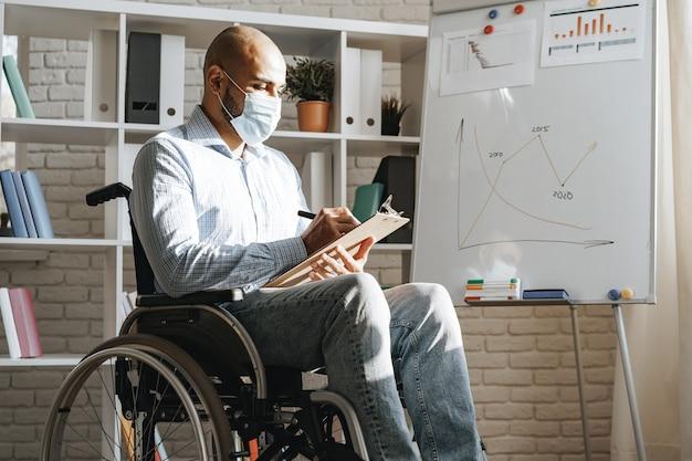 Niepełnosprawny młody człowiek robi prezentację w biurze nosząc maskę medyczną