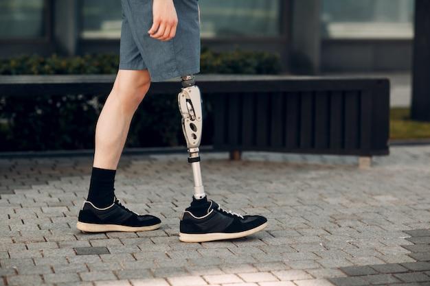 Niepełnosprawny młody człowiek z protezą stóp idzie ulicą.
