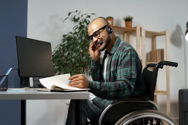 Niepełnosprawny młody mężczyzna na wózku inwalidzkim pracujący przy swoim stole roboczym z włączonym zestawem słuchawkowym