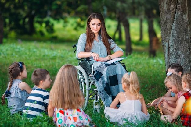 Niepełnosprawny nauczyciel prowadzi lekcję z dziećmi w przyrodzie. interakcja nauczyciela na wózku inwalidzkim z uczniami.