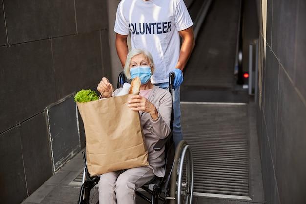 Niepełnosprawny rencista wyprowadzający się z domu towarowego na wózku inwalidzkim z pomocą opiekuńczego wolontariusza