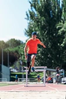 Niepełnosprawny sportowiec mężczyzna skoki z protezy nogi. koncepcja sportu paraolimpijskiego.