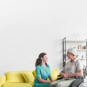 Niepełnosprawny starszy kobiety obsiadanie na koła krześle patrzeje pielęgniarki