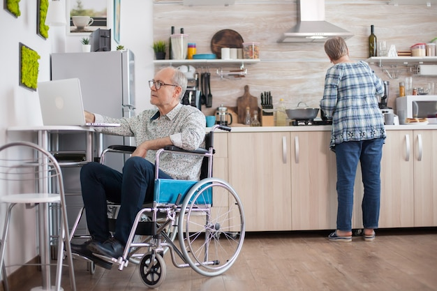 Niepełnosprawny starszy mężczyzna na wózku inwalidzkim pracuje na laptopie w kuchni, podczas gdy żona przygotowuje pyszne śniadanie dla obojga. człowiek korzystający z nowoczesnych technologii podczas pracy w domu.