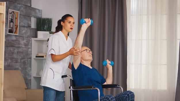 Niepełnosprawny starszy mężczyzna na wózku inwalidzkim robi fizjoterapeuta przy wsparciu terapeuty. osoba starsza niepełnosprawna niepełnosprawna z pracownikiem socjalnym w okresie rekonwalescencji terapia rehabilitacyjna fizjoterapia pielęgniarki opieki zdrowotnej