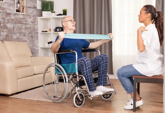 Niepełnosprawny starszy pacjent ćwiczący w domu z opaską oporową pod okiem pielęgniarki