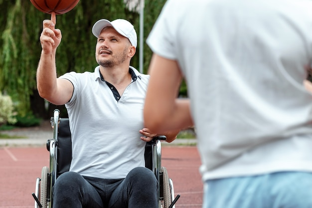 Niepełnosprawny tata bawi się z synem na ulicy. koncepcja wózka inwalidzkiego, osoba niepełnosprawna, spełnienie życia, ojciec i syn, aktywność, radość.