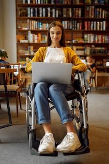 Niepełnosprawny uczeń na wózku inwalidzkim pracuje na laptopie