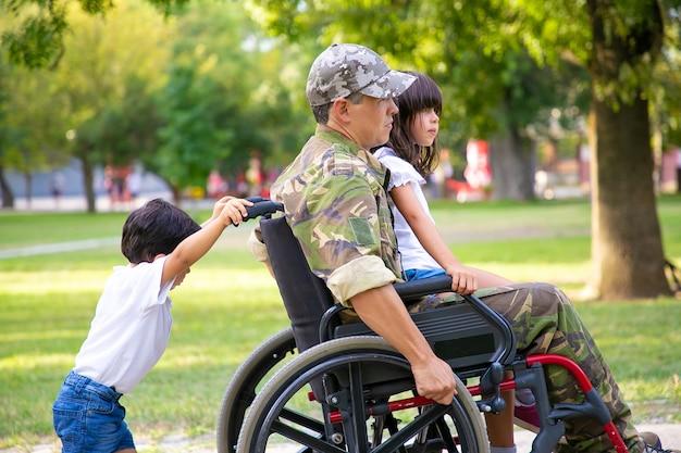 Niepełnosprawny weteran wojskowy spacerujący z dwójką dzieci w parku. dziewczyna siedzi na kolanach ojców, chłopiec pcha wózek inwalidzki. weteran wojny lub koncepcji niepełnosprawności