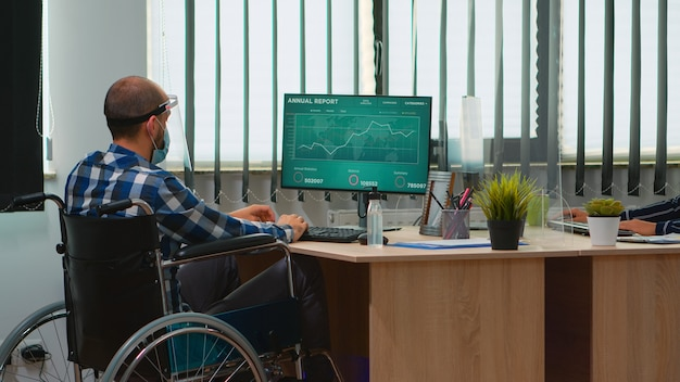 Niepełnosprawnych biznesmen siedzi na wózku inwalidzkim z maską ochronną do czyszczenia rąk przed sprawdzeniem danych finansowych w nowoczesnym biurze firmy. niepełnosprawny freelancer z przyłbicą szanującą dystans społeczny