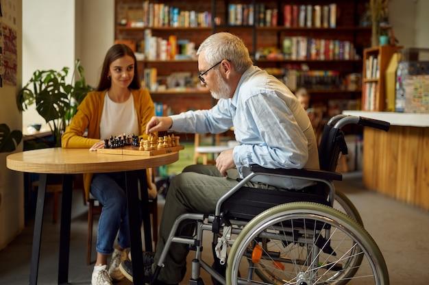 Niepełnosprawnych dziadek na wózku inwalidzkim i wnuczka grać w szachy, niepełnosprawność, wnętrze stołówki na tle. niepełnosprawny starszy mężczyzna i młoda pielęgniarka, sparaliżowani ludzie w miejscach publicznych