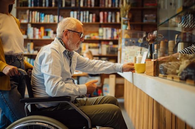 Niepełnosprawnych dziadek na wózku inwalidzkim i wnuczka w kasie, niepełnosprawność, wnętrze kawiarni na tle. niepełnosprawny starszy mężczyzna i młoda opiekunka, sparaliżowani ludzie w miejscach publicznych