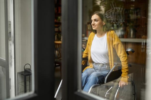 Niepełnosprawnych studentka na wózku inwalidzkim w oknie, niepełnosprawności, regał i wnętrze biblioteki uniwersyteckiej na tle. niepełnosprawna młoda kobieta studiująca na studiach, sparaliżowani ludzie zdobywają wiedzę
