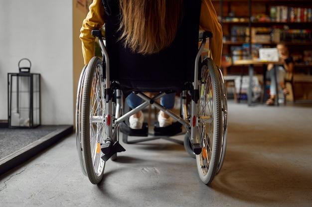 Niepełnosprawnych studentka na wózku inwalidzkim, widok z tyłu, niepełnosprawność, regał i wnętrze biblioteki uniwersyteckiej na tle. niepełnosprawna młoda kobieta studiująca na studiach, sparaliżowani ludzie zdobywają wiedzę