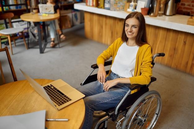 Niepełnosprawnych studentka na wózku inwalidzkim za pomocą laptopa, niepełnosprawności, regału i wnętrza biblioteki uniwersyteckiej na tle. niepełnosprawna młoda kobieta studiująca na studiach, sparaliżowani ludzie