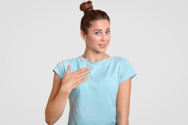Niepewna kobieta trzyma rękę na piersi, pytając, dlaczego została wybrana, stoi przy białej ścianie, nosi luźną koszulę, na białym tle nad białym. ludzie wątpią i nieśmiałość koncepcji.
