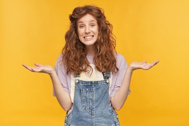 Niepewna, niepewna młoda rudowłosa suczka, z długimi falującymi włosami, uśmiecha się ze zdezorientowanym wyrazem twarzy, uniosła ręce na bok. na białym tle nad żółtą ścianą