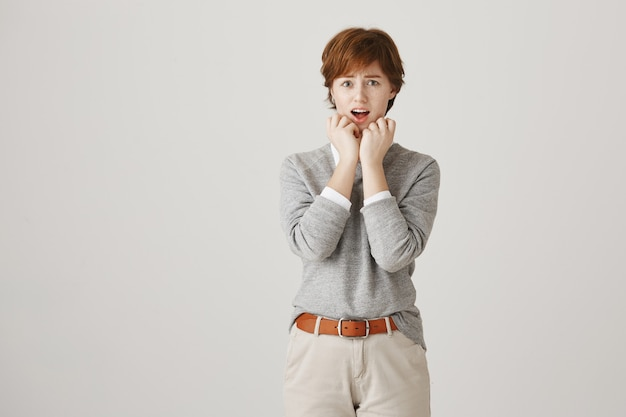 Niepewna zmartwiona ruda dziewczyna z krótką fryzurą pozuje na białej ścianie