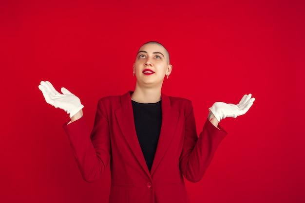Niepewność, pytanie. portret młodej kobiety kaukaski łysy na białym tle na ścianie czerwony studio.