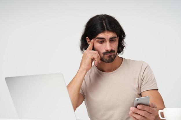 Niepewny facet, myślący biznesmen z czarnymi włosami i brodą. koncepcja biura. wzruszająca świątynia. patrząc na smartfona ze zdezorientowaną twarzą. siedząc w miejscu pracy, odizolowane z bliska na białej ścianie