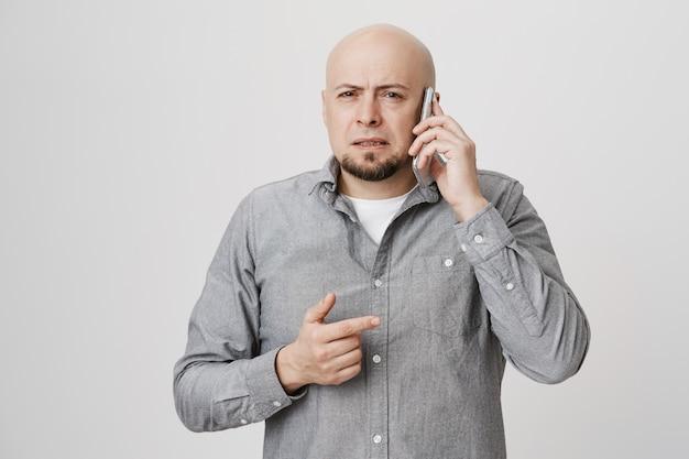 Niepewny łysy facet w średnim wieku, mrużący oczy i prowadzący rozmowę telefoniczną
