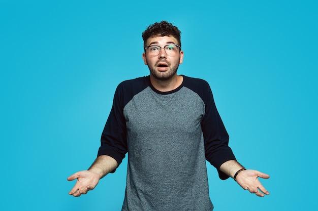 Niepewny młody człowiek wzrusza ramionami na białym tle nad niebieską ścianą