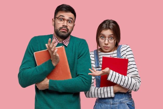 Niepewny, nieświadomy uczeń i uczennica patrzą z oburzeniem, niosą książkę i notatnik, nie wiedzą, jak przygotować projekt na temat szkolny