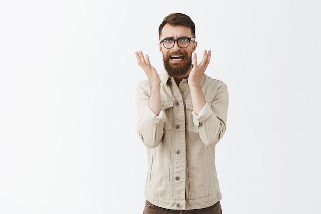 Niepewny panikujący brodaty mężczyzna w okularach pozuje na białej ścianie