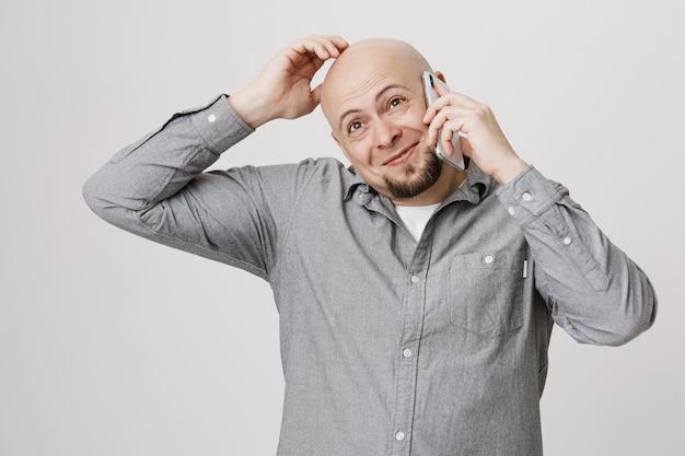 Niepewny, przemyślany łysy facet drapie głowę, rozmawiając przez telefon komórkowy