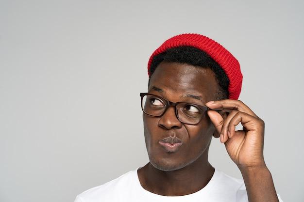 Niepewny wątpliwy afro amerykanin w czerwonym kapeluszu trzyma okulary