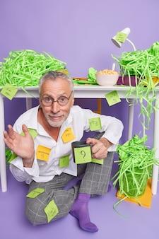 Niepewny, zdezorientowany, starszy mężczyzna, przedsiębiorca wygląda na przesłuchanego, robi listę rzeczy do zrobienia na naklejkach, pije kawę pozy w pobliżu pulpitu z zielonym wyciętym papierem wokół