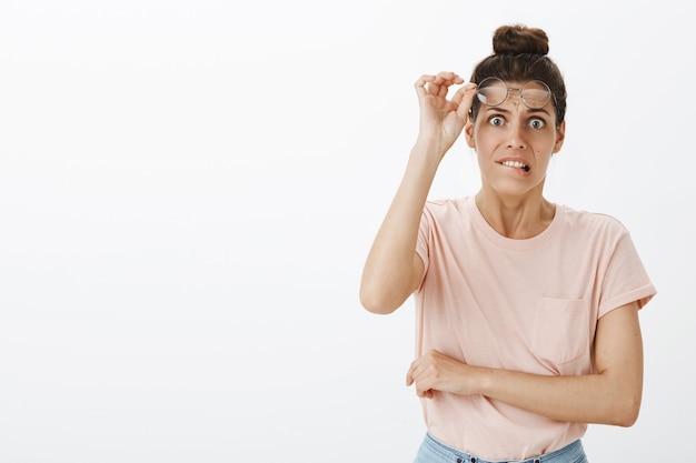Niepewny zmartwiony młoda stylowa kobieta pozuje na białej ścianie