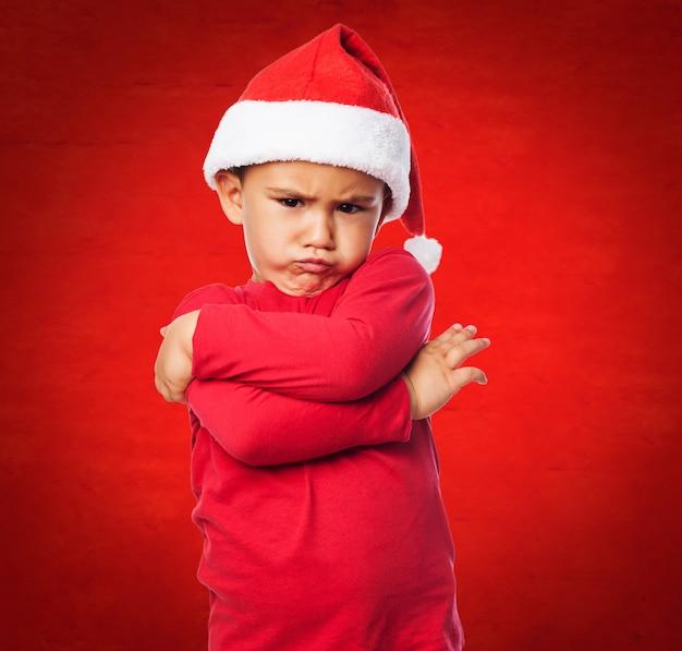 Niepokój dzieciak ze skrzyżowanymi ramionami i santa kapelusz
