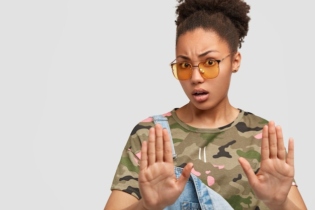 Niepokojąca kobieta w kamuflażu pozuje na białej ścianie