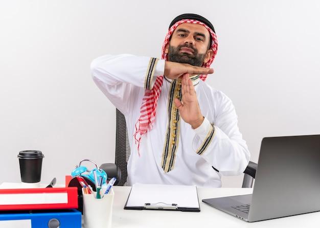 Niepokojący arabski biznesmen w tradycyjnym zużyciu siedzi przy stole z laptopem, robiąc gest z rękami do pracy w biurze