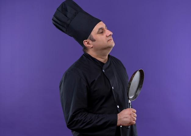 Niepokojący mężczyzna kucharz ubrany w czarny mundur i kapelusz kucharz trzymając owocowanie patelni stojący bokiem na fioletowym tle