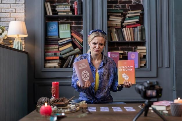 Niepolecane. miła młoda kobieta siedzi przed kamerą i opowiada o książkach, które jej się nie podobały