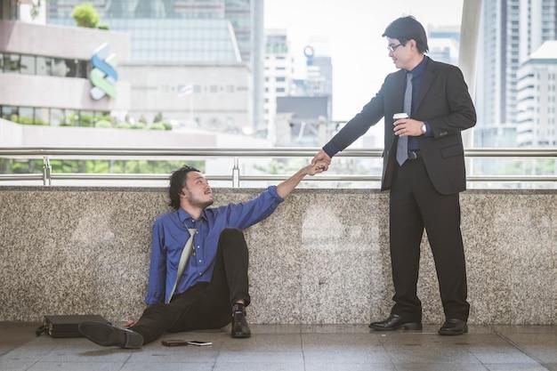 Niepowodzenie biznesmen bankrutujący próbuje wstać, gdy przyjaciel pomaga.