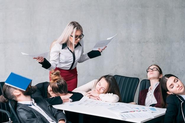 Niepowodzenie spotkania biznesowego. przepracowany stres. zdumiona kobieta z kadry kierowniczej patrząca na śpiących pracowników
