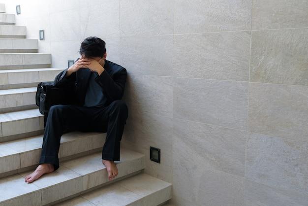 Niepowodzenie w biznesie młodzi biznesmeni siedzą na schodach, a jego dłonie zacisnęły się na głowie, ponieważ jest tak zdesperowany, zestresowany, smutek po poznaniu złych wieści, że jest bezrobotny.