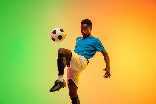 Niepowstrzymany afroamerykański męski piłkarz trenujący w akcji odizolowany na gradiencie