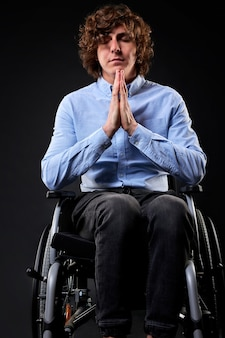 Nieprawidłowy niepełnosprawny mężczyzna modlący się z zamkniętymi oczami siedzący na wózku inwalidzkim, nadzieja na najlepsze, zdrowie. pojedyncze czarne tło