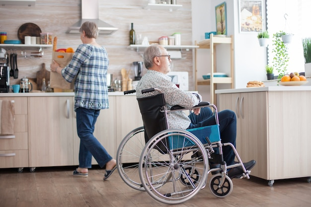 Nieprawidłowy starszy mężczyzna uśmiechający się patrząc przez okno w kuchni i żona rozpakowuje artykuły spożywcze. inwalida, rencista, inwalida, paraliż.