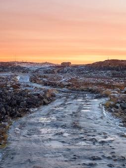 Nieprzejezdna oblodzona droga przez zimową tundrę. w oddali ciągnęła się wyboista, kamienista droga. półwysep kolski.