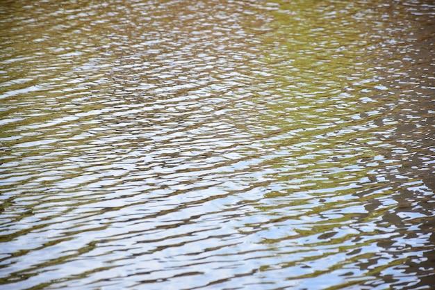 Nieprzejrzysta tafla wody jeziora lub rzeki z niewielkimi zmarszczkami na całej klatce