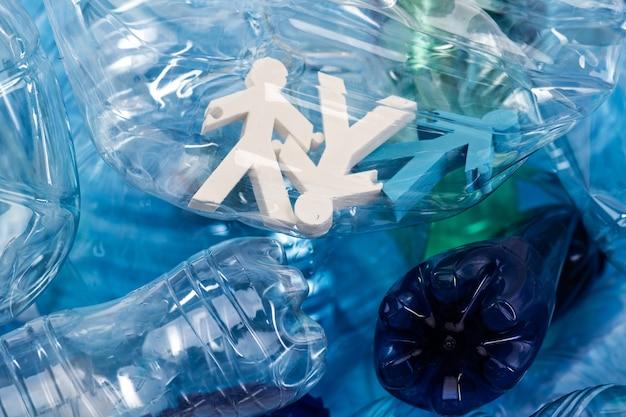 Nieprzetworzone plastikowe śmieci. kolorowe postacie ludzi umieszczone w plastikowej butelce jako ofiary globalnej konsumpcji