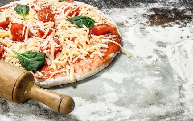 Nieprzygotowana pizza z dodatkami. na rustykalnym tle.