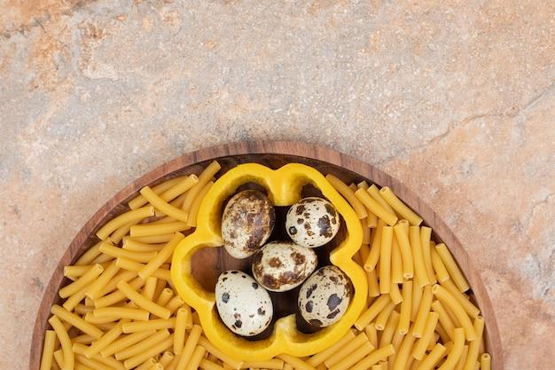 Nieprzygotowany makaron z pieprzem plasterek i jajkami przepiórczymi na drewnianym talerzu. wysokiej jakości zdjęcie