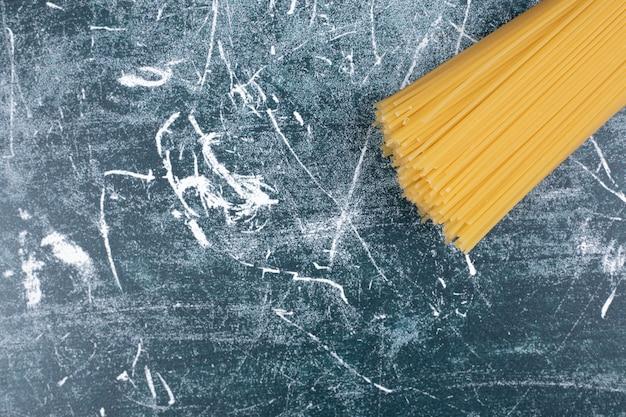 Nieprzygotowany pęczek makaronu spaghetti pełnoziarnistego związany liną na marmurowym tle